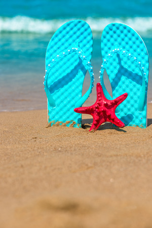 Vertical shot of beach shoes and starfish on the sea photo