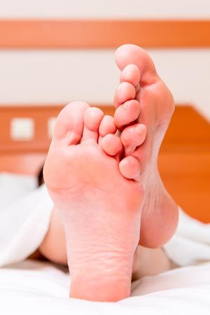 Barfuß weibliche Füße im Bett stillsteht