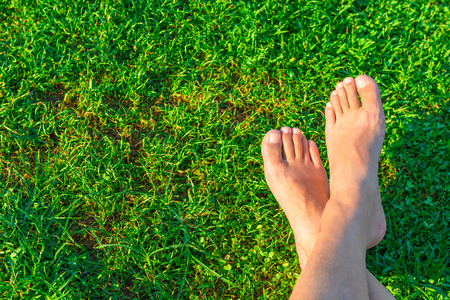 Mens feet on the background of lush green grass