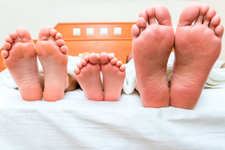 family of three people sleeping in one bed, feet close-up Stockfoto