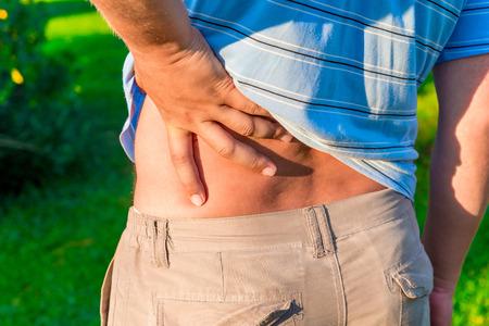 dolor de espalda: hombre que sostiene su mano dolorida espalda baja