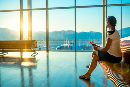 lounge chairs: girl at the airport waiting for boarding Stock Photo