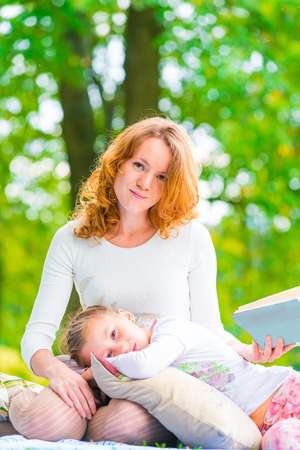 Vertical portrait of a mother and daughter in the park photo