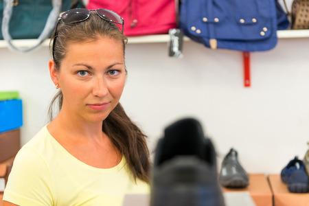 buying shoes: chica joven hace una compra en la tienda con los zapatos