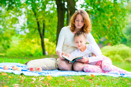 mother reads her daughter an interesting book in the park photo