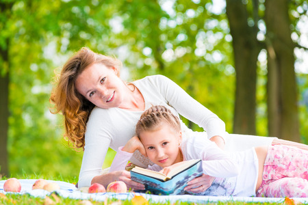 Mom and daughter reading a book lying in the park photo