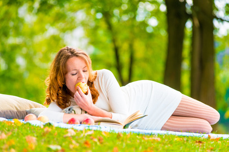 Red-haired student eats an apple and reading books in the park photo