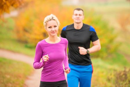 hombre fuerte: mujer y hombre en parque del oto�o en correr por la ma�ana