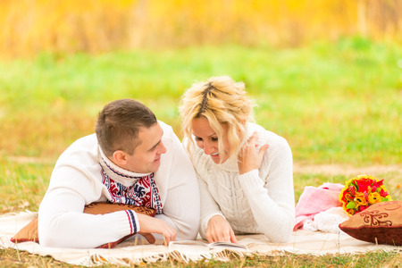 couple on a picnic together reading a novel photo