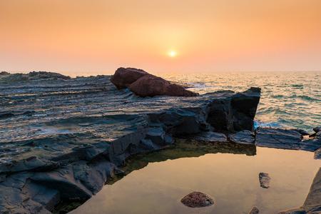 hardened: hardened lava and ocean at sunset Stock Photo