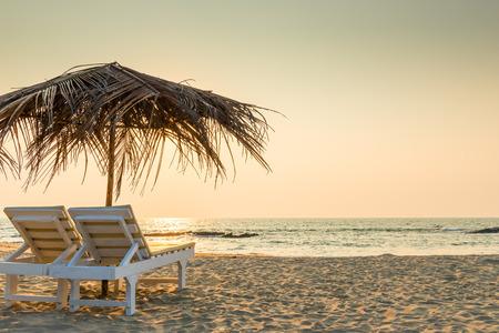 strandstoel: lege stoelen onder rieten parasols op een zandstrand Stockfoto