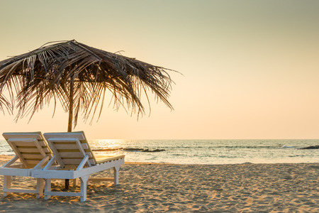 silla de madera: sillas vac�as bajo las sombrillas de paja en una playa de arena Foto de archivo