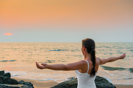 lifestyle caucasian: girl with his hands spread apart at sunset by the sea Stock Photo