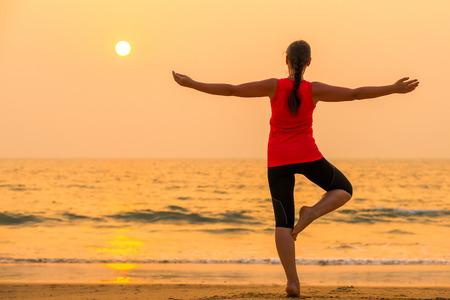 girl on background of the sea balance on one leg