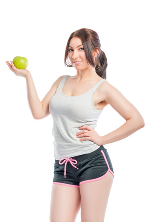 sports form: attractive girl in the sports form with green apple