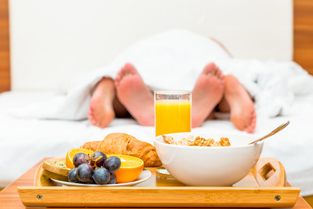 couple in bed, a tray of food in focus Stockfoto