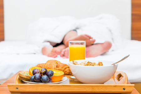 couples feet luxuriate in bed and a tray of food