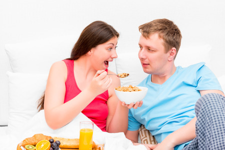 young wife: wife feeding her husband breakfast in bed