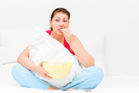 attentively: Brunette attentively watching television and eating popcorn