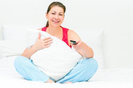 ver television: mujer abrazando una almohada y ver la televisi�n