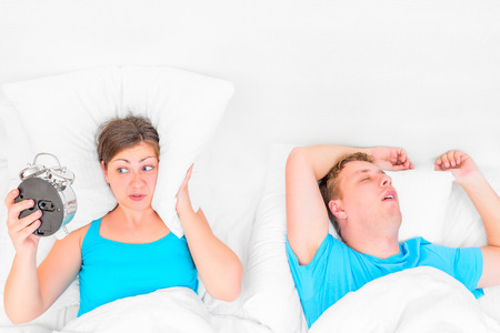 snoring: woman with an alarm clock listening to the snoring husband