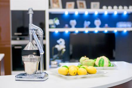 juicer: steel citrus juicer on the kitchen table Stock Photo