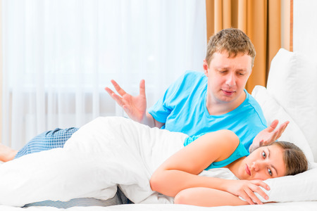 wife: man scolds his wife in bed at night Stock Photo