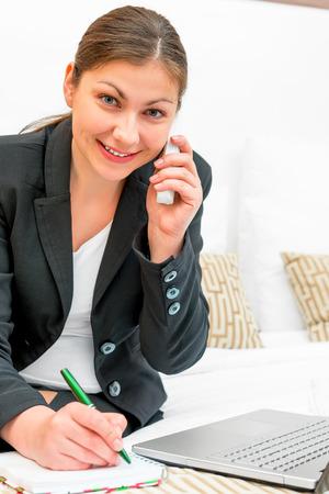erfolgreiche frau: erfolgreiche Frau in einem Anzug am Telefon zu sprechen und machte sich Notizen in einem Notebook