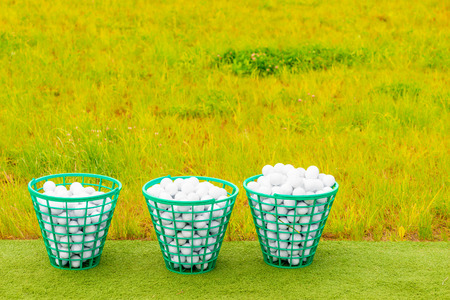 three baskets filled with golf balls on the green grass Stockfoto