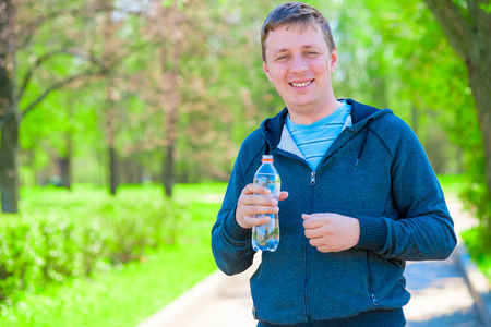 workouts: portrait of a happy trainer with a bottle of water during a break between workouts Stock Photo