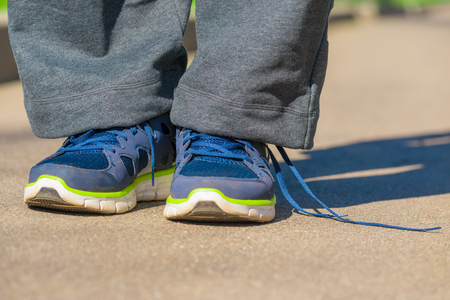 untied: men feet in sneakers with untied lace Stock Photo