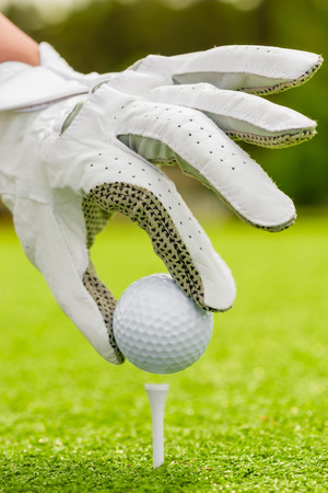 golf tee: womans hand neatly puts the ball on tee on field Stock Photo