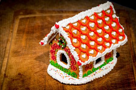 casita de dulces: casa de jengibre bellamente decorado se encuentra en una mesa de madera