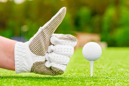 golf green: Positive hand gesture near the golf ball on a tee