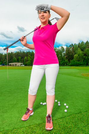 looking behind: beautiful woman on a golf course looking behind a flying ball Stock Photo