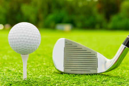 golf balls: White ball on tee and golf club on the field