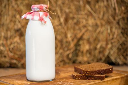 vaso de leche: botella de leche y un pedazo de pan de centeno en un fondo de la paja Foto de archivo