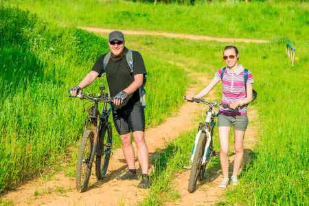 heterosexual couple: happy young couple walking with bicycles Stock Photo