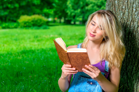 cute blonde: portrait of a student with a book in the park