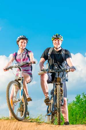 road cycling: Vertical shot of a smiling couple on a bicycle