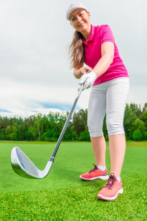 golf swings: Vertical shot girl golfer before impact