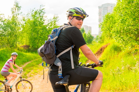 recreational: Male cyclist in helmet with a backpack and his girlfriend Stock Photo