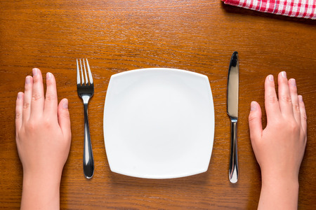 wooden plate: female hands near empty plate on the table Stock Photo
