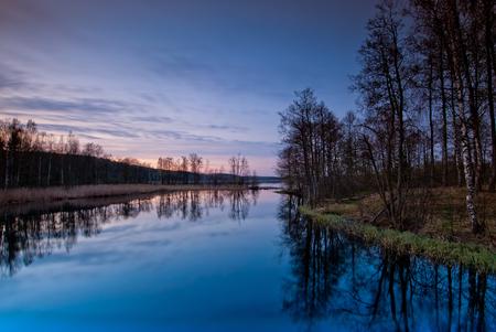 nature scenery: beautiful landscape at sunset. Bare trees around calm lake