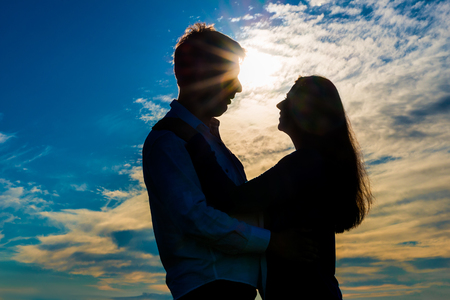 couple lit: silhouette of a loving couple hugging at sunset
