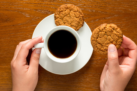 women holding cup: hands holding a cup of coffee and cookies top view