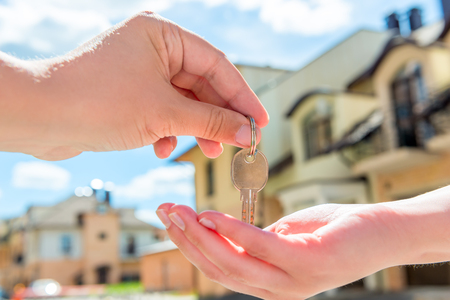 sale: transfer to the buyer of the house key close-up of hands against the sky