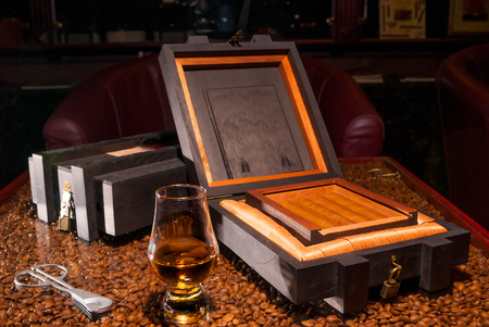 scotch whisky: luxury Cuban cigars in a box and a glass of alcohol