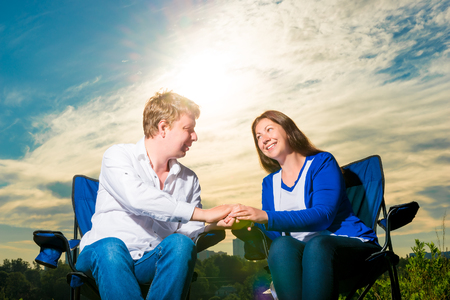 couple lit: portrait of happy loving couple at sunrise on chairs outdoors Stock Photo