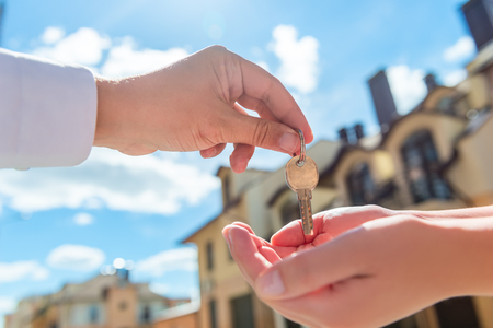 customer focus: the seller transfers key to the house in the hands of the buyer outdoors
